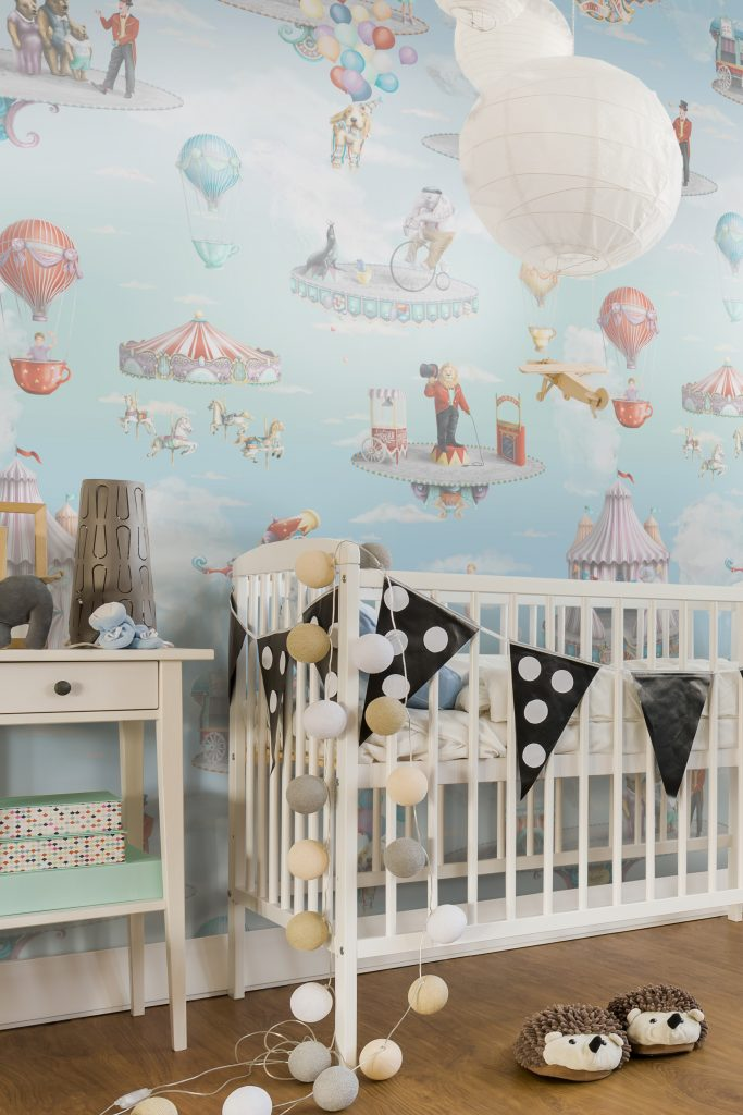 This is a circus wallpaper theme. Set in the sky with planes and clouds and flying objects. It is a unisex wallpaper design perfect for kids bedroom or nursery. Styled here with white cot and cirucs animal themes.