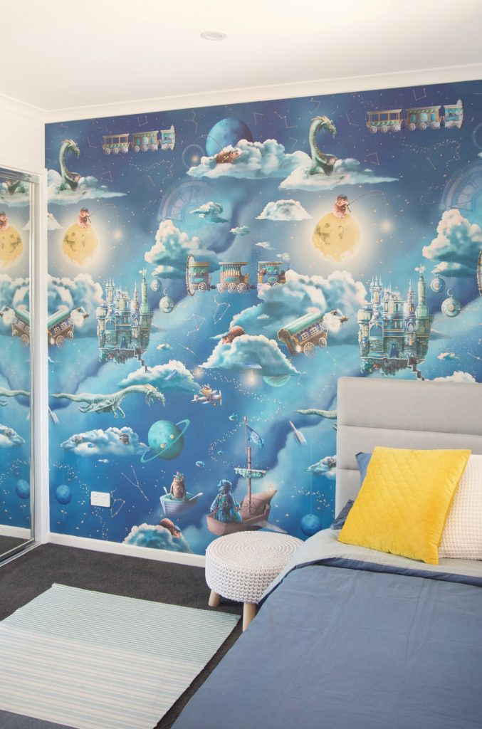Kids galaxy interior wallpaper design. Features a night sky space theme with moon, clouds, dragon, compass, fishing and fairy tale creatures. In blue colours styled with a grey bed and yellow cushion.