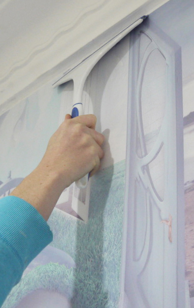 A detailed wallpaper installation guide for paste-the-wall heavy duty vinyl wall coverings! Our instructions are clear and easy to follow. Photo shows how to used a squeegee to smooth down wallpaper.