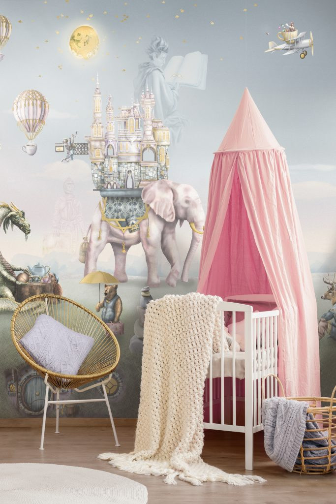 The most gorgeous nursery! Featuring our fairy tale custom wallpaper wall mural. The bedroom features pink bed canopy, gold feature rattan chair and pastel decor.