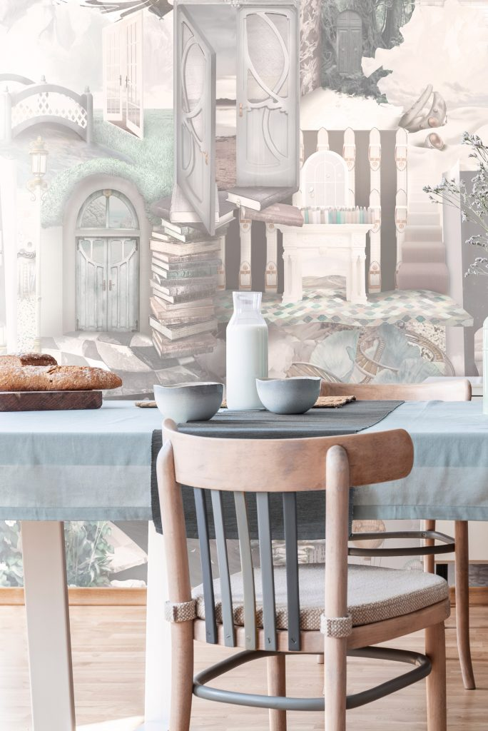 Fun modern wallpaper in warm cozy and inviting colours. Brown, sepia, beige, mint, blue base. An interior family wallpaper design suited for living lounge kitchen room. Styled on country wood dining table with mint vase, berries and bread.