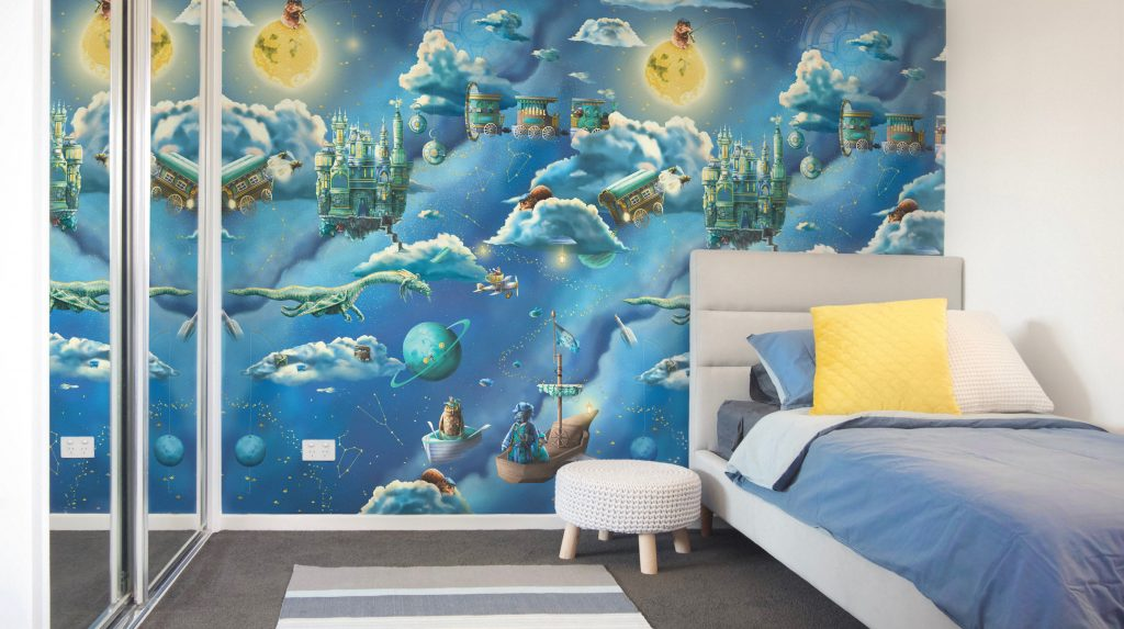 Boys Nursery Themes Ideas. Space and Galaxy Kids Interior Wallpaper Design - featuring a grey blue and white bedroom with custom kids wallpaper. Wallpaper features the moon, night sky, clouds, pirate ships, flying trains, stars, dragon, galaxy and more. Set in colours of Navy Blue, Turquoise, Gold and yellow.